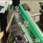 Konsis konveyör yuvarlak şişe üzerine çevresel etiketleme konveyör uygulaması..